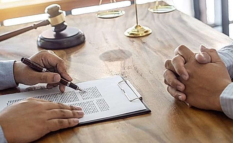 two people signing papers at the table